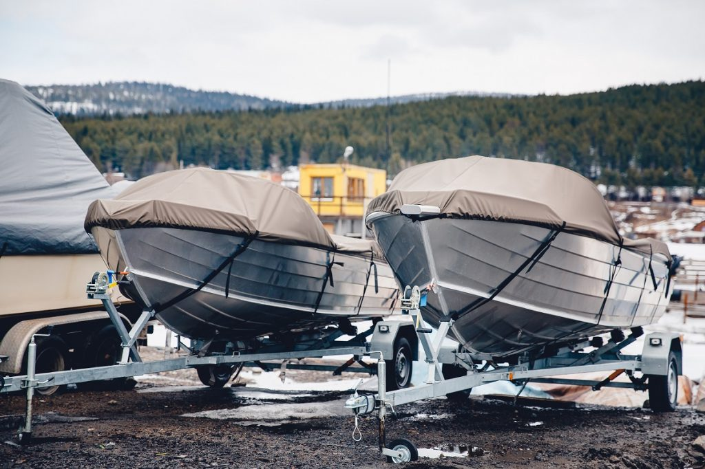 Covered boats on steel pontoon trailers