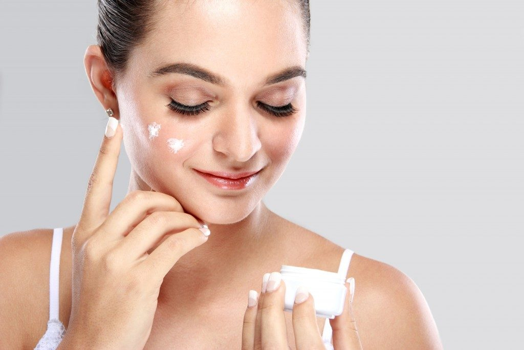 Woman applying cream skin care