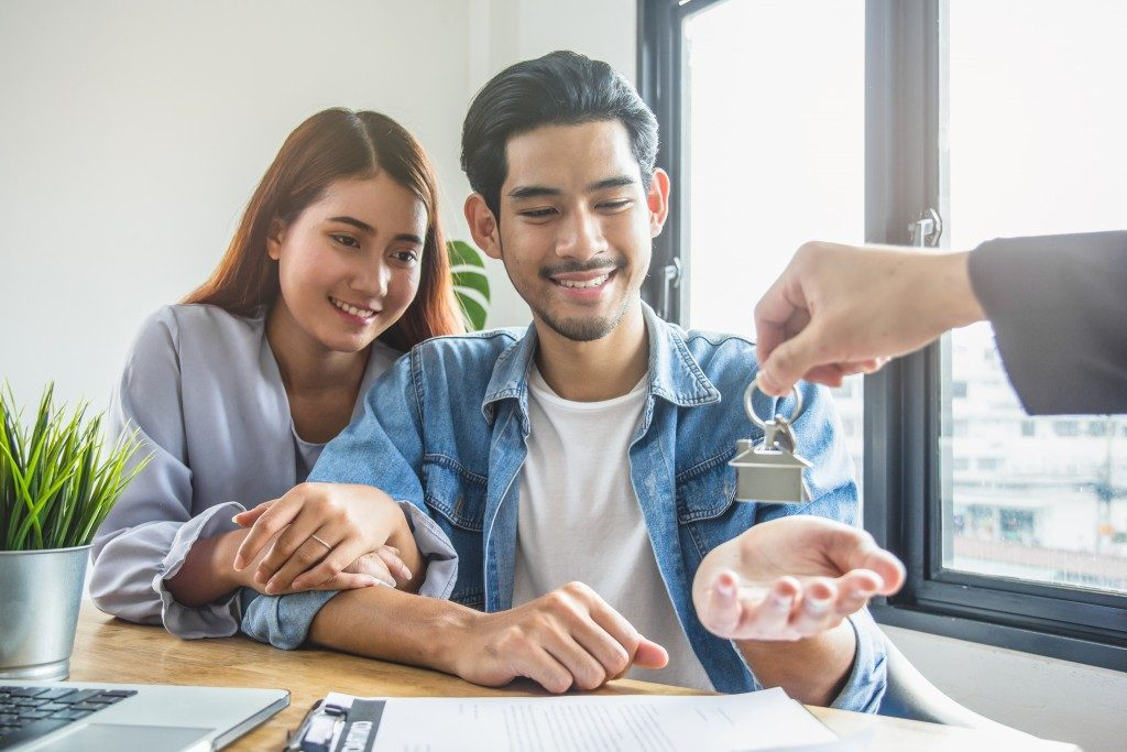 Young couple receiving apartment keys
