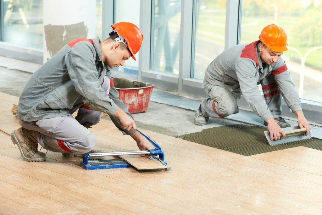 construction workers installing floor tiles